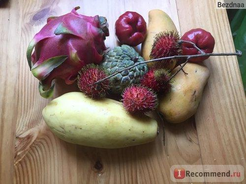 Большая зеленая папайя, 2 желтых манго, большой малиновый драконов фрукт, посередине зеленая аннона, волосатые красные рамбутаны, гладкие красные забыла